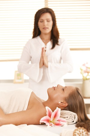 Woman lying on massage bed, masseur meditating in background. photo