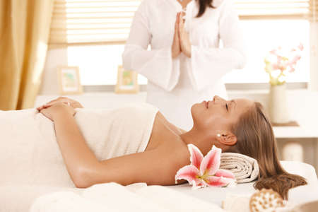 Woman lying on massage bed, masseur meditating in background. Stock Photo - 8141804