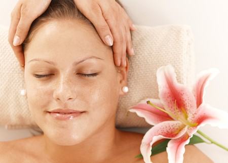 Closeup of portrait of young woman getting relaxing head massage, smiling. photo