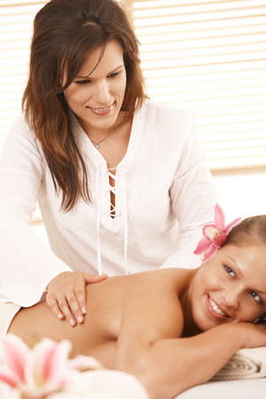 Masseur doing deep tissue massage, looking at guest, smiling. photo