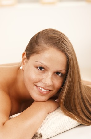 Closeup portrait of beautiful young woman lying on massage bed, smiling. Stock Photo - 8141795