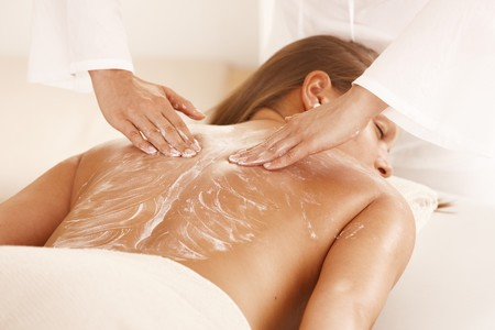 mujeres de espalda: Masajista aplicar crema de masaje en la espalda de la mujer joven.  Foto de archivo