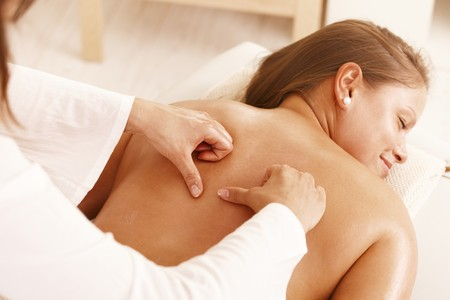 Smiling young woman getting back massage in day spa. photo