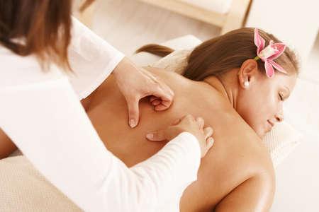 Closeup of masseurs hands doing massage treatment. photo