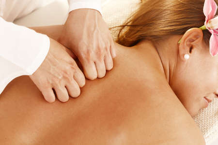 Closeup photo of masseurs hands pressing young womens back during massage treatment. photo