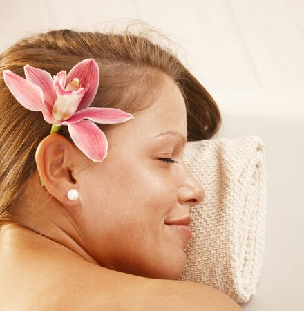 Closeup portrait of beautiful young woman relaxing in spa, smiling. photo
