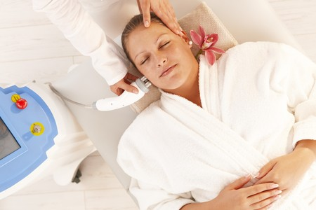 radio frequency: Young woman getting radio frequency fat reduction treatment in day spa, smiling. Stock Photo