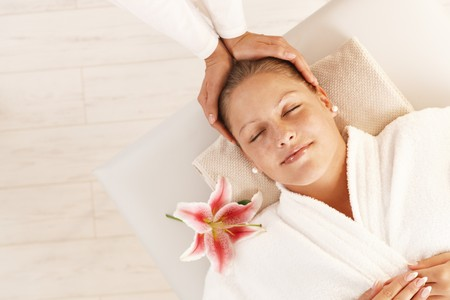 Woman enjoying relaxing head massage in dayspa with closed eyes. photo