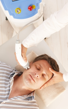 Man getting radio frequency fat reduction treatment in day spa. photo