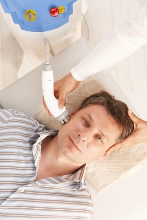 Mid-adult man getting radio frequency fat reduction treatment in spa. Stock Photo - 8141757