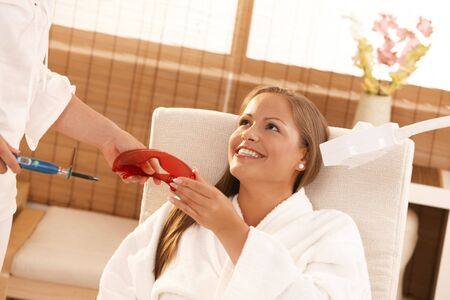 Young woman preparing for laser tooth whitening treatment at spa. photo