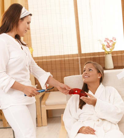 Beautician handing over safety googles before laser tooth whitening treatment at spa. Stock Photo - 8141811