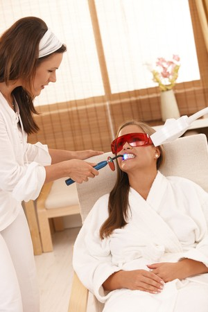 Beautician doing cosmetic laser tooth whitening treatment at beauty saloon. photo