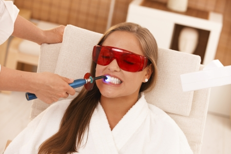 bleach: Young woman getting laser tooth whitening treatment at spa. Stock Photo