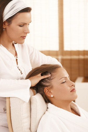 sitting room: Woman getting relaxing head massage with closed eyes.