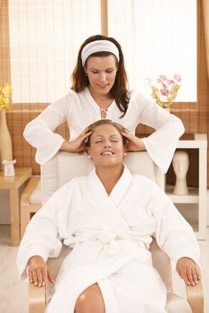 Happy woman enjoying head massage with closed eyes, smiling. photo