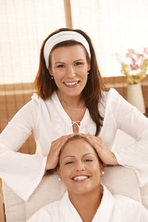 beauty therapist: Happy masseur doing head massage, looking at camera, smiling.