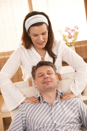massage chair: Man sitting in chair, enjoying massage with closed eyes, smiling.
