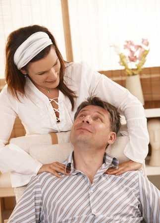 Man getting neck massage, looking up at masseur, smiling. photo