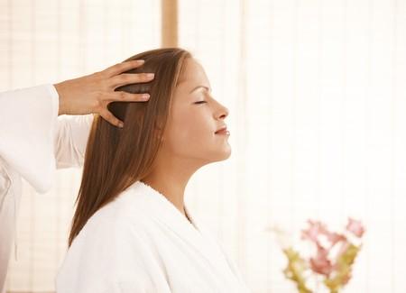 Portret van jonge vrouw genieten van hoofd massage met gesloten ogen, glimlachend.