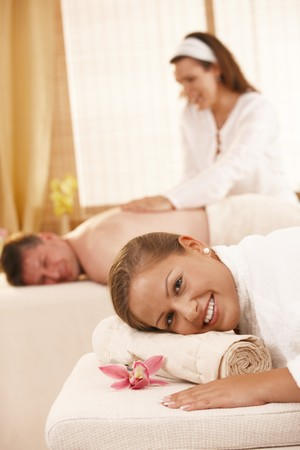 Happy couple getting back massage in day spa. photo