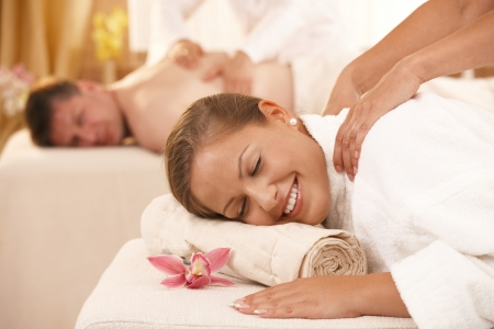 back massage: Happy couple having back massage in day spa. Stock Photo
