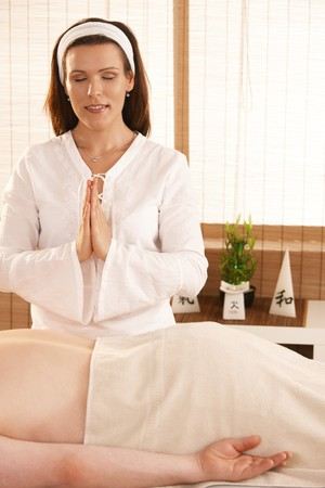 Masseur meditating over patient, preparing for massage. Stock Photo - 8141773