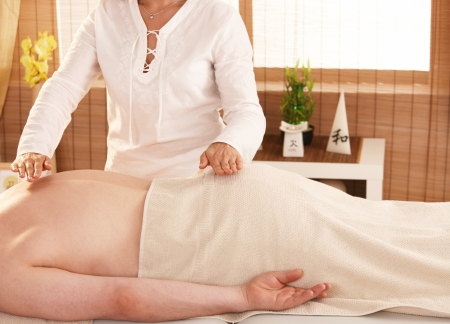 reiki: Hands over patientt back during reiki treatment. Stock Photo