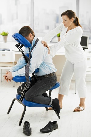 mujeres sentadas: Empresario sentado en el sill�n de masaje, volviendo masaje.