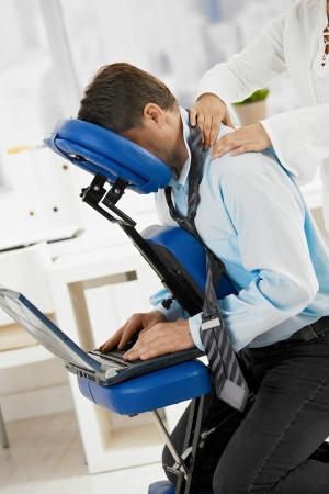 adult massage: Businessman sitting on massage chair, getting back massage.