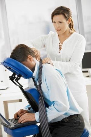 mujeres sentadas: Empresario sentado en el sill�n de masaje, volviendo masaje.  Foto de archivo