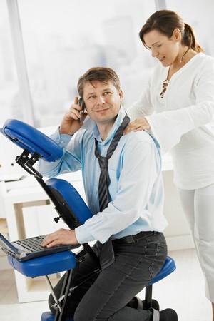 hombre sentado: Empresario hablando por el m�vil al obtener el masaje de cuello en la Oficina.  Foto de archivo