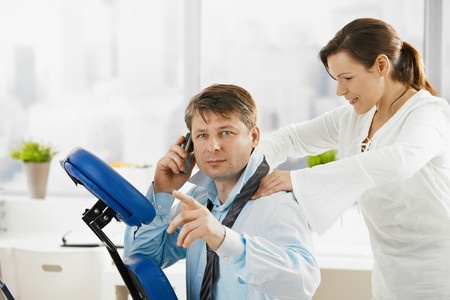 Businessman talking on mobile while getting neck massage in office.