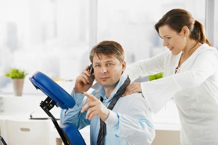 massaggio collo: Imprenditore parlando sul telefonino mentre ottenere massaggio collo in ufficio.