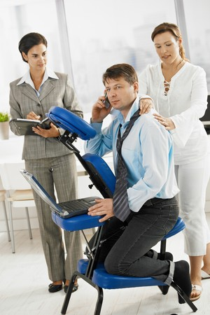 neck collar: Businessman talking on mobile while getting neck massage in office.