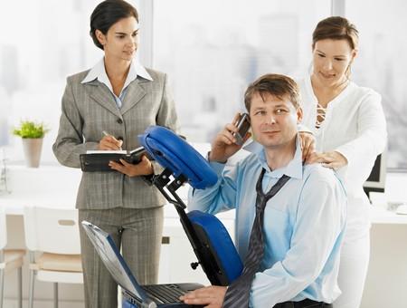 hombre sentado: Ejecutivo ocupado hablando por el m�vil al obtener el masaje de cuello en la Oficina. Secretario esperando en el fondo.