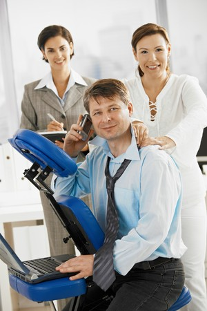 massage chair: Occupied executive continue working while getting back massage in office.
