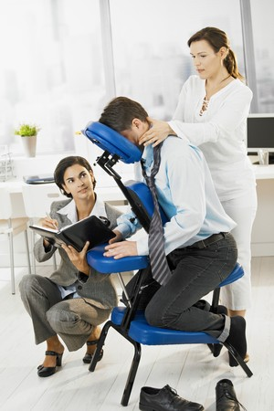 Occupied executive continue working while getting back massage in office. Stock Photo - 8305210