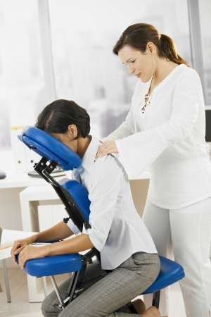 Businesswoman sitting on massage chair, getting back massage.