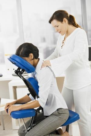masoterapia: Empresaria sentado en el sillón de masaje, volviendo masaje.