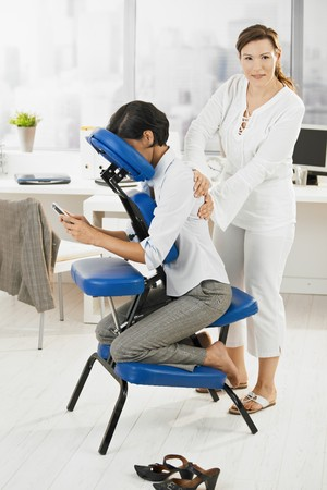 Businesswoman sitting on massage chair, getting back massage. photo