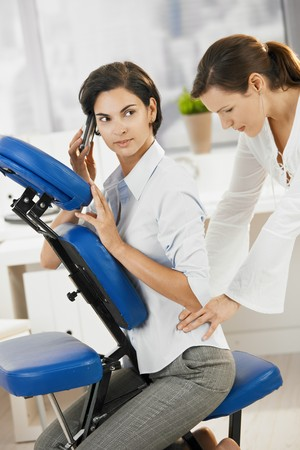 doing business: Businesswoman talking on mobile while getting neck massage in office.