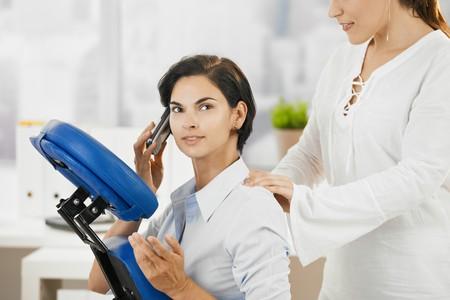 massaggio collo: Occupati businesswoman parlando sul telefonino mentre ottenere massaggio collo in ufficio.