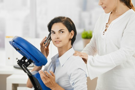 massage chair: Occupied businesswoman talking on mobile while getting neck massage in office.
