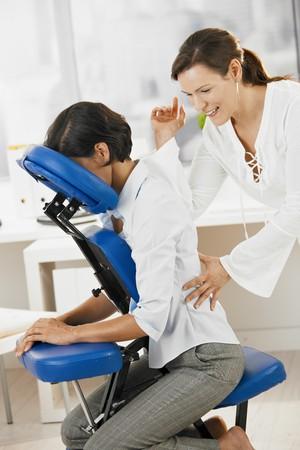 massaggio: Businesswoman seduto sulla poltrona da massaggio, godendo di massaggio alla schiena.