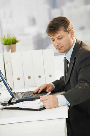 Businessman sitting at desk, writing notes to organizer and using laptop computer. Stock Photo - 8141776