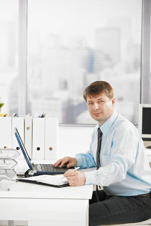 Businessman at work, searching in personal organizer, using laptop. Looking at camera. photo