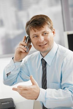 Portrait of businessman in office, talking on smartphone, gesturing. photo
