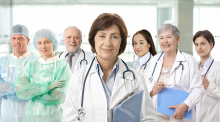 Team of medical professionals lead by senior female doctor looking at camera, smiling.