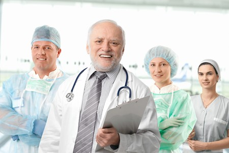 medical assistant: Team of medical professionals lead by senior white haired doctor looking at camera, smiling.